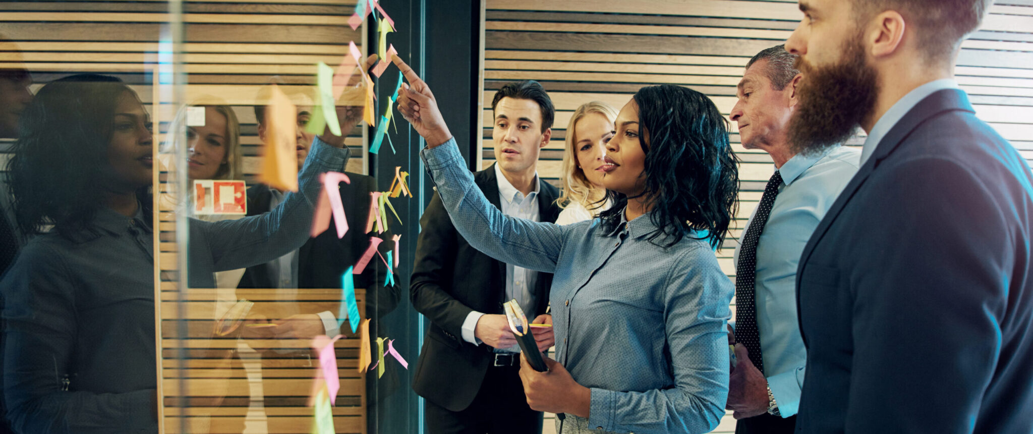 Woman pointing to post-it notes on office board